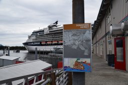 Ketchikan Downtown District Sign on Salmon Landing area with Cruise Ship in the Background